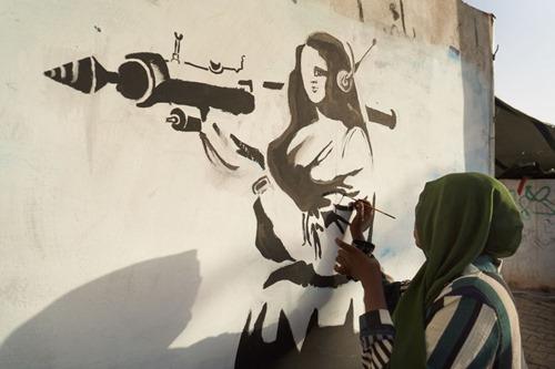 safa-al-hadi-paints-satirical-graffiti-at-the-sit-in-site - Suc May article thumbnail